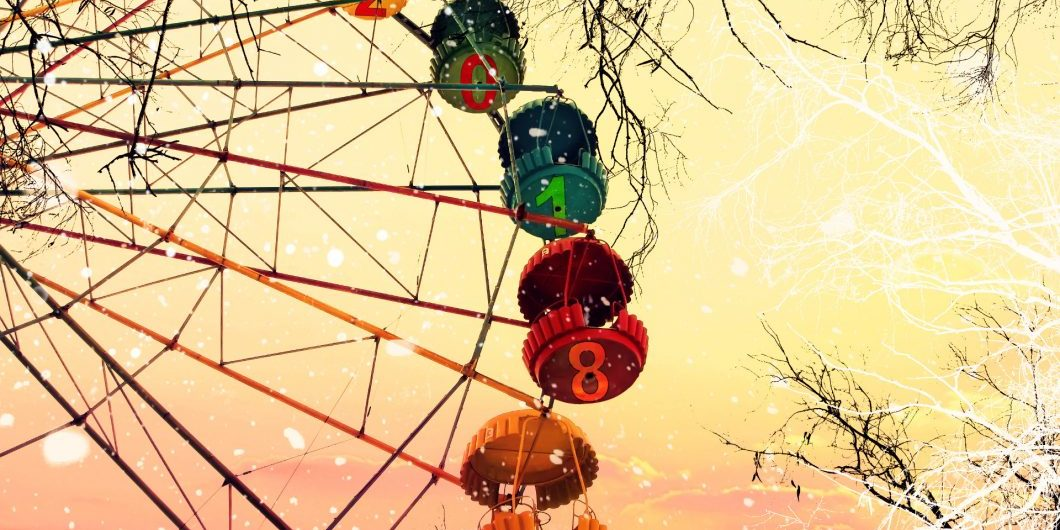 New year 2018. Two thousand eighteen. Ferris wheel. Naked trees under a snowfall against sunrise sky. Winter dream
