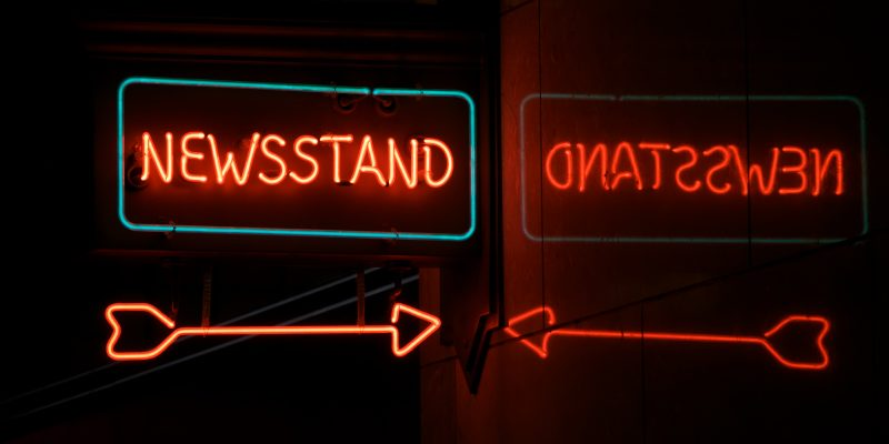 neon-newsstand-with-arrow-and-reflection-by-GarysFRP-via-istockphoto