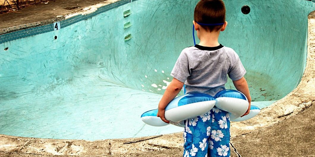 small-boy-looking-at-empty-pool-by-ricklordphotography-via-istock